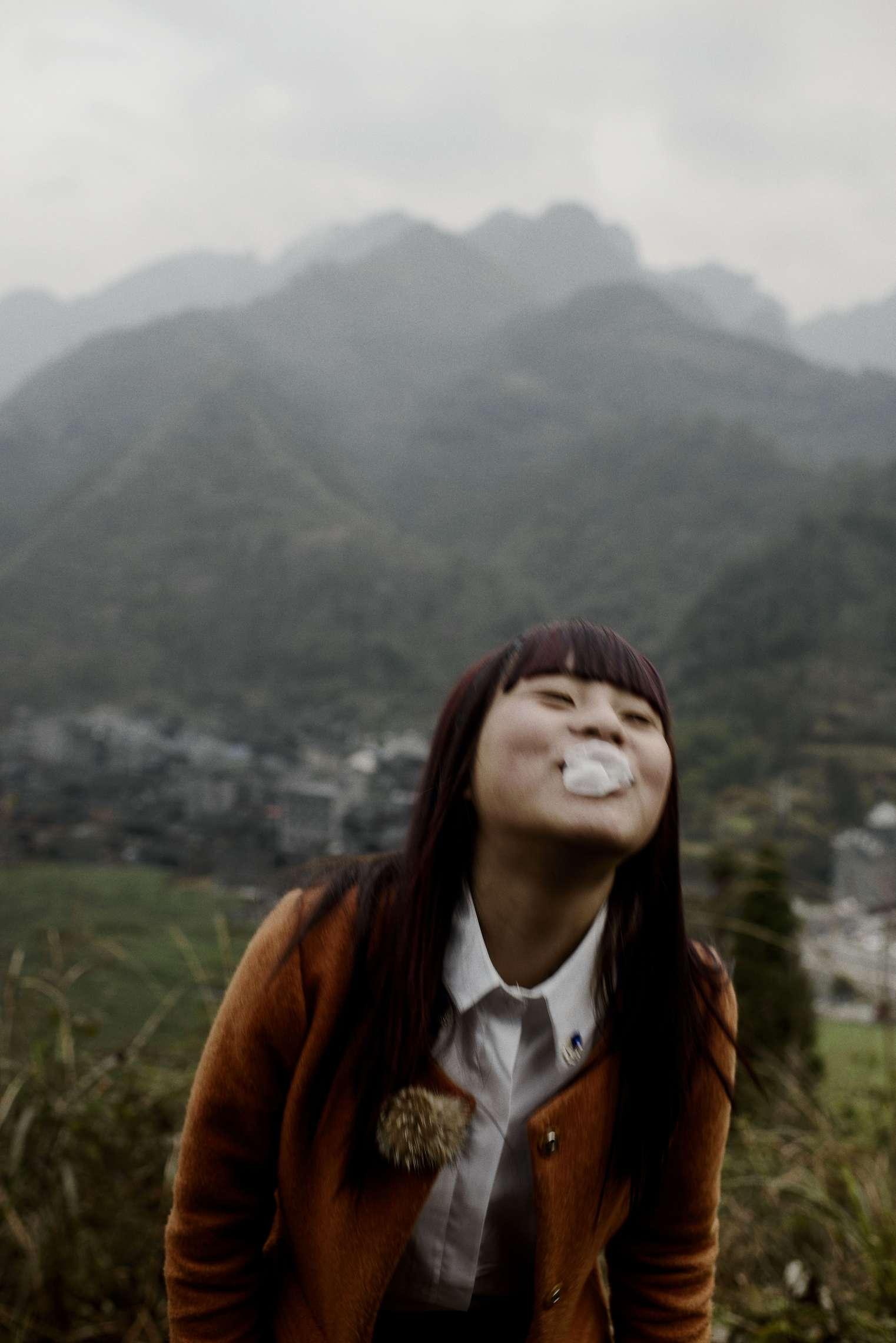 PK-nr: 10968 Kategori: 8, dokumentar utlandDato: 23.02.2015 Tittel: Hun reiser i morgen Hovedtekst: Siden 1978 har Kina opplevd den største folkevandringen i verdenshistorien. Nærmere 160 millioner kinesere har reist fra lutfattige landsbyer for å finne arbeid i byene. I fjellandsbyen Hangsha i Hunan provinsen, står Rong Shi Yu (14) på klippen sammen med barndomsvenninnene sine, hånd i hånd på høye hæler, mens de blåser rosa bobler. De synger om gutter de ennå ikke vet hvem er, som skal gjøre dem lykkelige, og kanskje velstående. De synger om å høre til her i Lu Dong-fjellene, men i morgen pakker de trillekoffertene, reiser fra alt de kjenner, mot kysten og storbyene. Der venter Kinas mest effektive fabrikker med ti kroner i timen, ti timer hver dag. Men der venter også mulighetene for økonomisk uavhengighet. Bildetekst: Så lenge Rong Shi Yu (14) kan huske, har moren satt seg på toget etter feiringen av det kinesiske nyttår. Nå har Rong også droppet ut av skolen. I morgen pakker hun trillekofferten for å jobbe i de mange tekstilfabrikkene ved Kinas kyst. Hun er annengenerasjons arbeidsimmigrant.