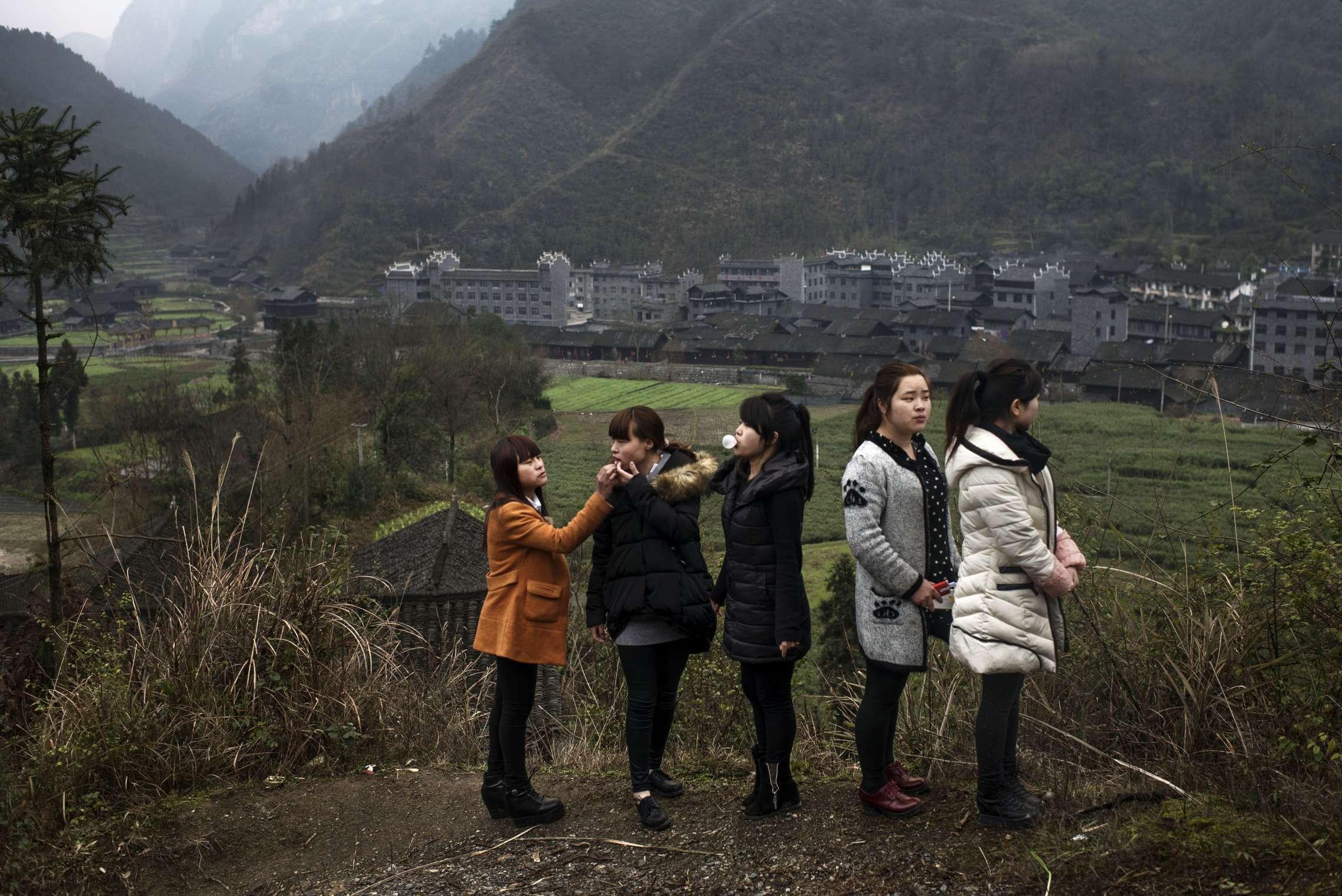PK-nr: 10968 Kategori: 8, dokumentar utlandDato: 23.02.2015 Tittel: Hun reiser i morgen Hovedtekst: Siden 1978 har Kina opplevd den største folkevandringen i verdenshistorien. Nærmere 160 millioner kinesere har reist fra lutfattige landsbyer for å finne arbeid i byene. I fjellandsbyen Hangsha i Hunan provinsen, står Rong Shi Yu (14) på klippen sammen med barndomsvenninnene sine, hånd i hånd på høye hæler, mens de blåser rosa bobler. De synger om gutter de ennå ikke vet hvem er, som skal gjøre dem lykkelige, og kanskje velstående. De synger om å høre til her i Lu Dong-fjellene, men i morgen pakker de trillekoffertene, reiser fra alt de kjenner, mot kysten og storbyene. Der venter Kinas mest effektive fabrikker med ti kroner i timen, ti timer hver dag. Men der venter også mulighetene for økonomisk uavhengighet. Bildetekst: Mens bøndene venter på vårregnet, har venninnegjengen funnet sitt faste møtepunkt med utsikt over landsbyen de har vokst opp i. De har ikke sett hverandre på ett år. De fleste forlot Hangsha for å arbeide da de var 15 år. Fra venstre: Shi Yu Rong (14), Shi Yu Zheng (18), Shi Si Hua (26), Shi Yu Pun (23) og Shi Pi Hua (22).