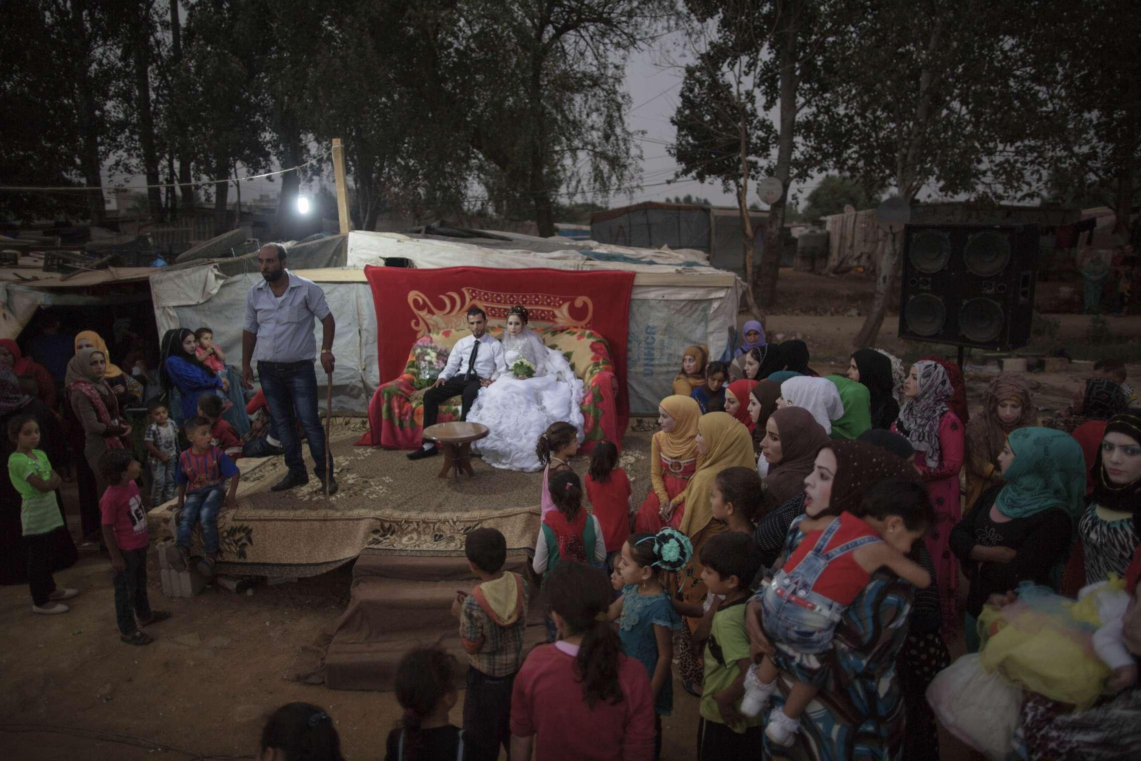00619 14. Årets fotojournalist 06.09.2015 Bryllup i flyktningleiren Det syriske flyktningparet Samir (24) og Shrook Nazal (20) gifter seg i flyktningleiren Housein Meraar i Beka'a dalen i Libanon, nær grensen til Syria. Alle de andre flyktningene i leiren har bidratt til å lage bryllupet, hvor det danses, synges og feires til langt på natt. Bryllupet er en sjelden dag med glede og feiring i livet til flyktningene i leiren, hvor nesten alle er fra den IS-kontrollerte syriske byen Raqqa. I Libanon bor mer enn 1 million syriske flyktninger, og de utgjør dermed mer enn 25 prosent av landets befolkning. Hundrevis av små og store flyktningleire ligger i Zahle-provinsen, nær grensen til Syria. På grunn av lavere bistand fra medlemslandene, har FN vært nødt til å kutte nødhjelpen til flyktningene. Mange av leirene mangler helt basale ting som helsetjenester, rent vann, toaletter og undervsining.